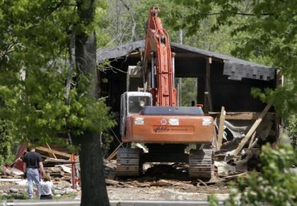 Demolition workers tear down a horse barn for the FBI during the search for former Teamster's Union president Jimmy Hoffa's body at the Hidden Dreams Horse Farm May 24, 2006 in Milford, Michigan. The FBI received a tip, reportedly from Donovan Wells who lived on the farm, that the Hoffa was buried on the farm. (Photo by Bill Pugliano/Getty Images