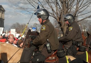 Mounted police in riot gear are seen among right-to-work protesters. (credit: WWJ/Ron Dewey)