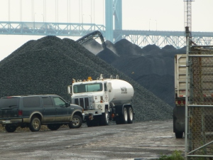 This photo shows pet coke being dumped onto a growing pile of the material near the Detroit River in southwest Detroit on Tuesday. (credit: Pat Sweeting/WWJ)