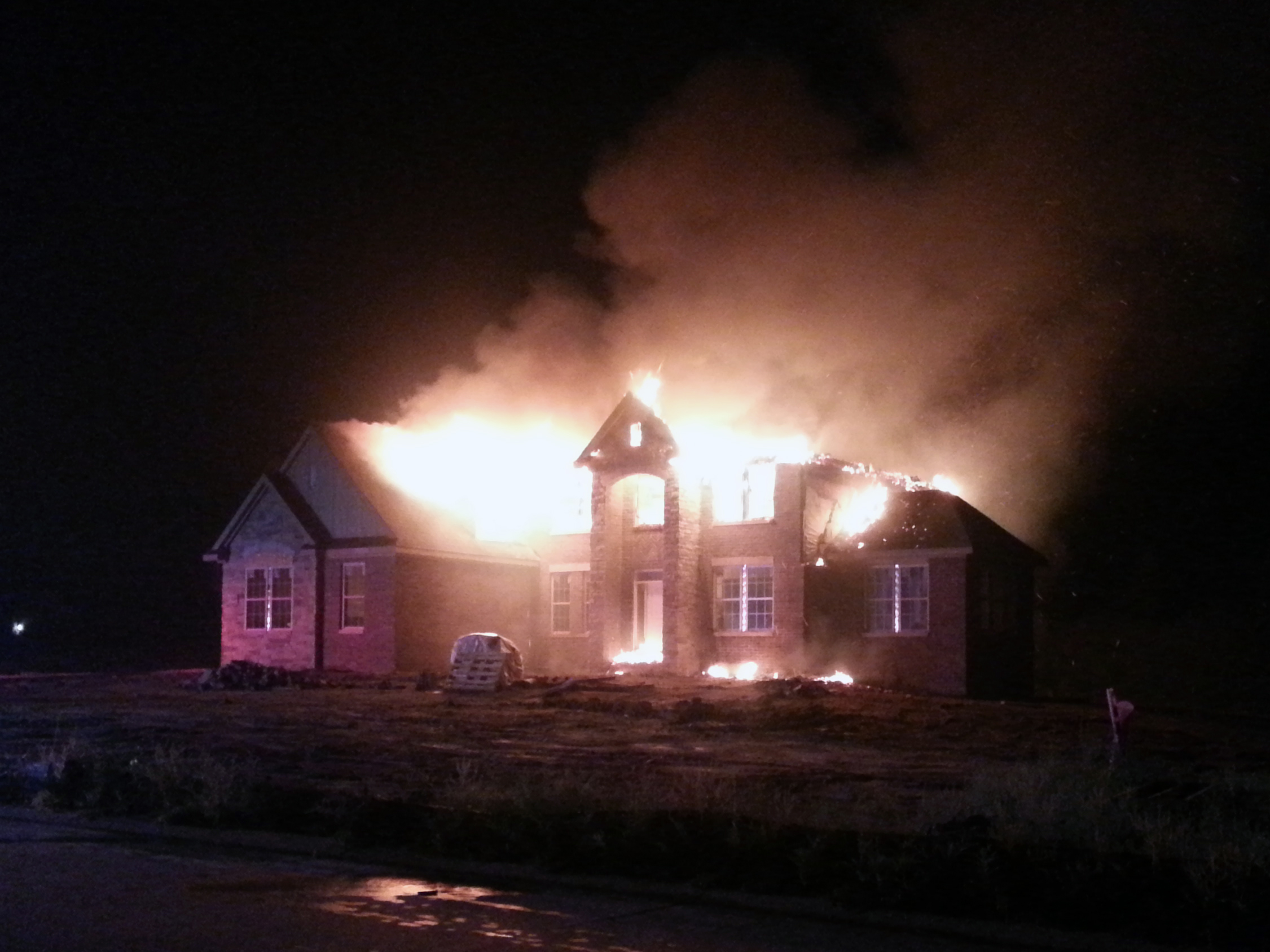 This brand new home under construction in Lyon Township went up in flames after lightning reportedly struck the house. (Credit: Jon Hewett/WWJ Newsradio 950)