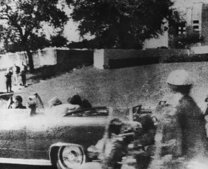 American president John F. Kennedy (1917 - 1963) is struck by an assassin's bullet as he travels through Dallas in a motorcade November, 22 1963. In the car next to him is his wife Jacqueline (1929 - 1994) and in the front seat is Texas governor John Connally. (Credit: Three Lions/Hulton Archive/Getty Images)