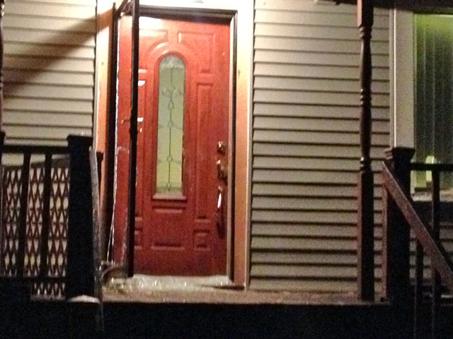 Shattered glass from a storm door cover a west side Detroit porch following a shooting. (Credit: Mike Campbell/WWJ Newsradio 950)