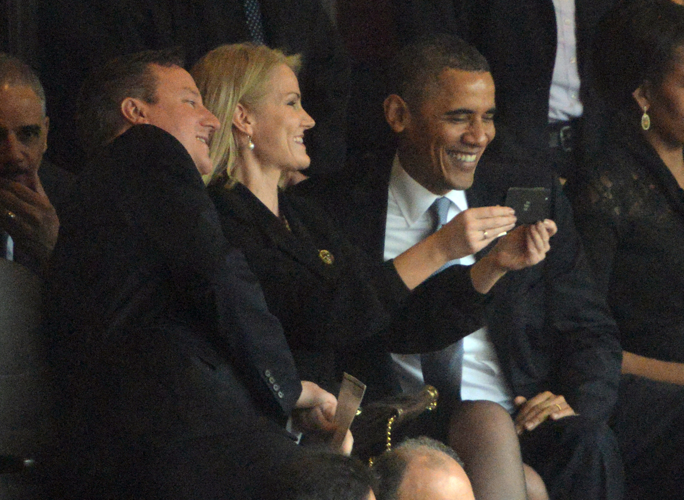US President Barack Obama (R) and British Prime Minister David Cameron pose for a picture with Denmark's Prime Minister Helle Thorning Schmidt (C) during the memorial service of South African former president Nelson Mandela at the FNB Stadium (Soccer City) in Johannesburg on December 10, 2013. Mandela, the revered icon of the anti-apartheid struggle in South Africa and one of the towering political figures of the 20th century, died in Johannesburg on December 5 at age 95. AFP PHOTO / ROBERTO SCHMIDT        (Photo credit should read ROBERTO SCHMIDT/AFP/Getty Images)