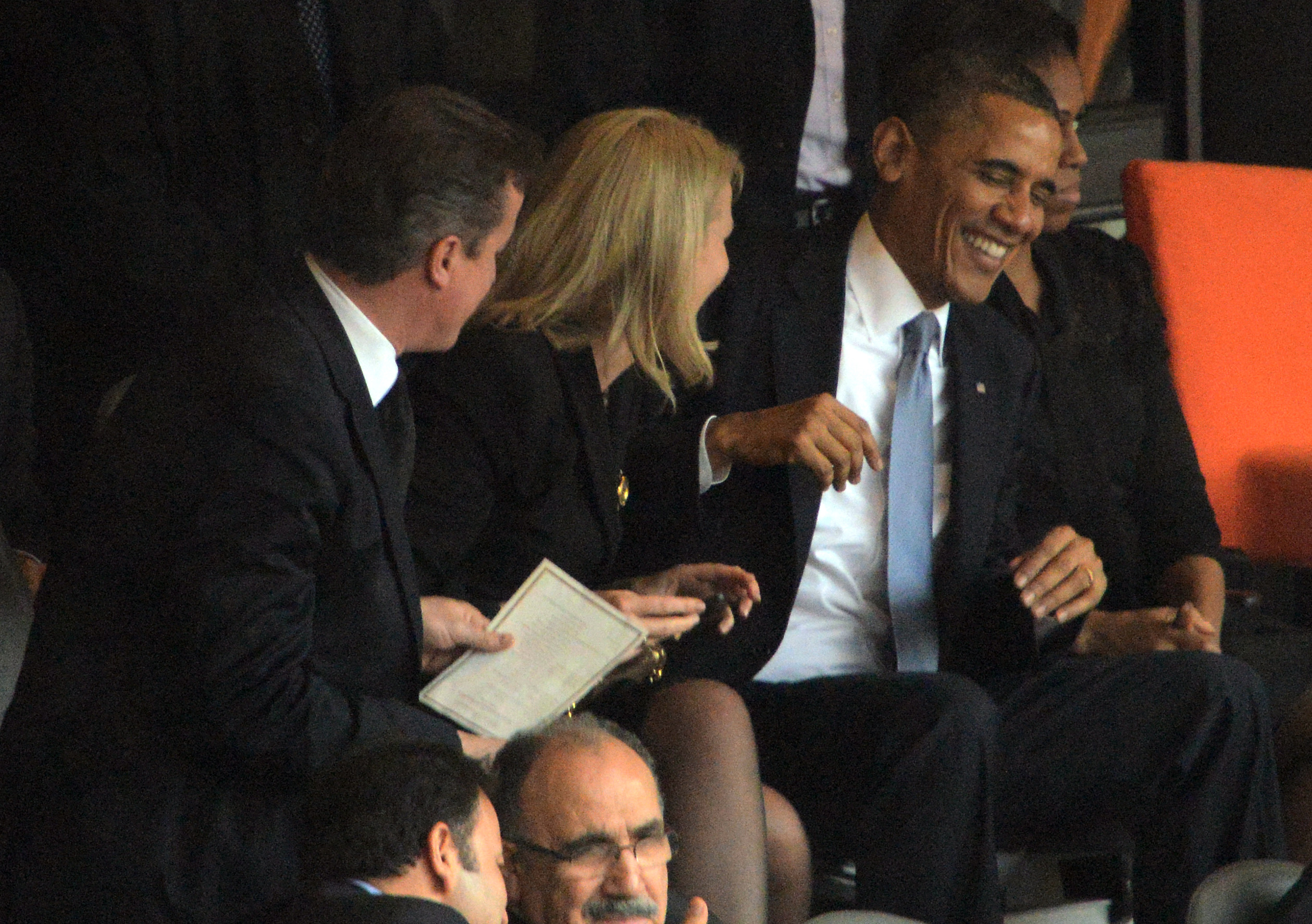 US President Barack Obama (R) smiles before posing for a picture with British Prime Minister David Cameron and Denmark's Prime Minister Helle Thorning Schmidt (C) during the memorial service of South African former president Nelson Mandela at the FNB Stadium (Soccer City) in Johannesburg on December 10, 2013. Mandela, the revered icon of the anti-apartheid struggle in South Africa and one of the towering political figures of the 20th century, died in Johannesburg on December 5 at age 95. AFP PHOTO / ROBERTO SCHMIDT        (Photo credit should read ROBERTO SCHMIDT/AFP/Getty Images)