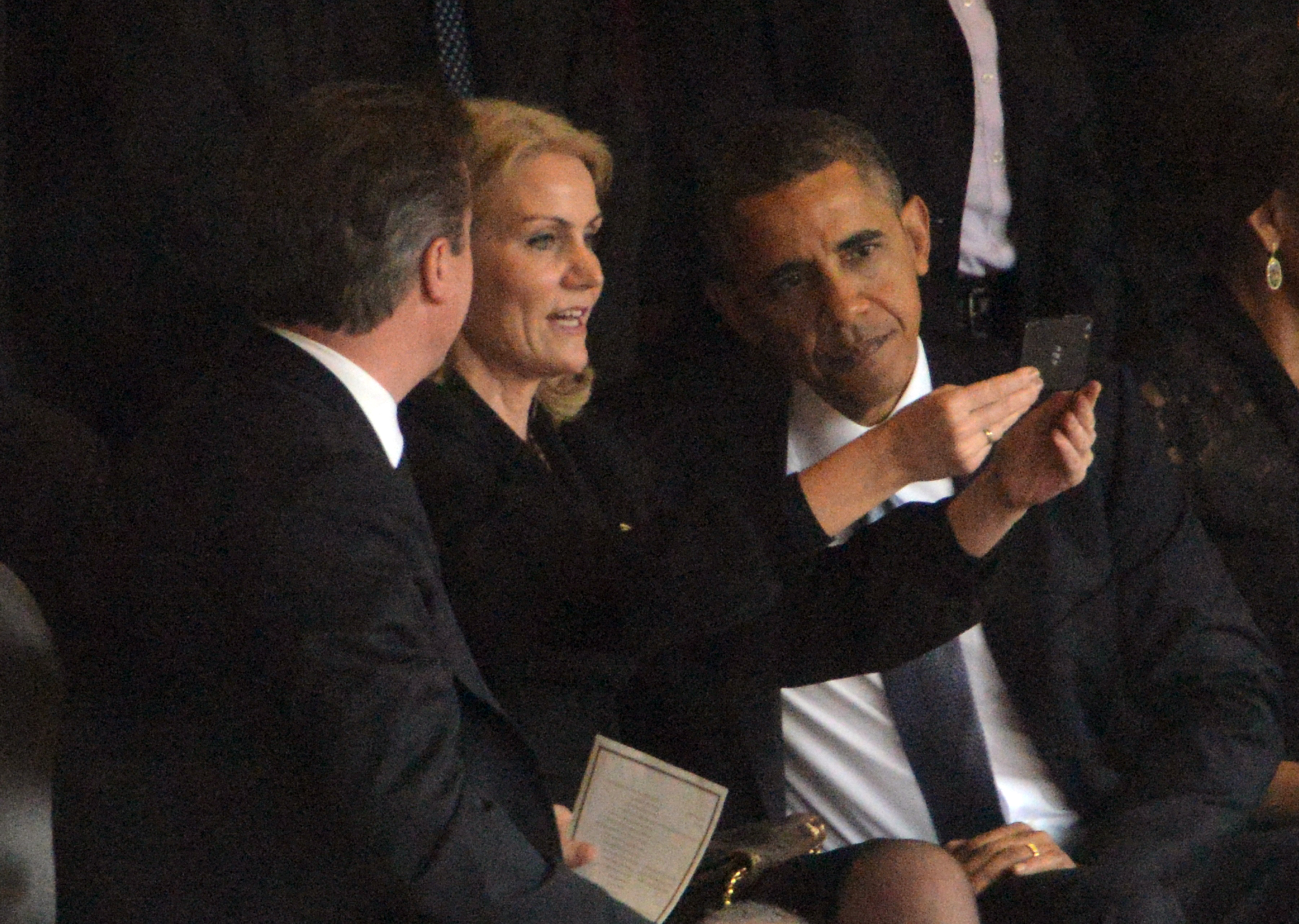 US President Barack Obama (R), British Prime Minister David Cameron look at the picture taken by Denmark's Prime Minister Helle Thorning Schmidt (C) during the memorial service of South African former president Nelson Mandela at the FNB Stadium (Soccer City) in Johannesburg on December 10, 2013. Mandela, the revered icon of the anti-apartheid struggle in South Africa and one of the towering political figures of the 20th century, died in Johannesburg on December 5 at age 95. AFP PHOTO / ROBERTO SCHMIDT        (Photo credit should read ROBERTO SCHMIDT/AFP/Getty Images)