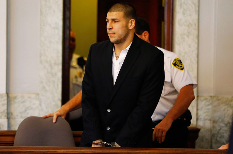 NORTH ATTLEBORO, MA - AUGUST 22: Aaron Hernandez is escorted into the courtroom of the Attleboro District Court for his hearing on August 22, 2013 in North Attleboro, Massachusetts. Former New England Patriot Aaron Hernandez has been indicted on a first-degree murder charge for the death of Odin Lloyd.
