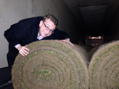 WWJ's Charlie Langton just couldn't keep his hands off of the fresh Kentucky bluegrass, soon to cover the field at Comerica Park. (Credit: WWJ Newsradio 950)