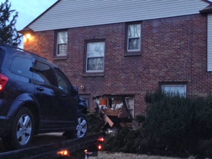 A suspected getaway car is pulled from the side of a home on Detroit's west side after an apparent home invasion and shooting. (Credit: Mike Campbell/WWJ Newsradio 950)