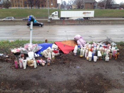 A makeshift memorial was created along the I-75 service drive where three teens were killed when the stolen vehicle they were driving crashed onto the freeway below. (Credit: Mike Campbell/WWJ Newsradio 950)