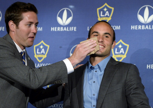 Brendan Hannan wipes lipstick from the right cheek of Landon Donovan of the Los Angeles Galaxy after he announced his retirement following the 2014 MLS season during a news conference at the StubHub Center on August 7, 2014, in Carson, California. (Photo by Kevork Djansezian/Getty Images)