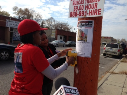 Julia Spencer hangs Crime Stoppers fliers on Detroit's east side. (credit: Vickie Thomas/WWJ)