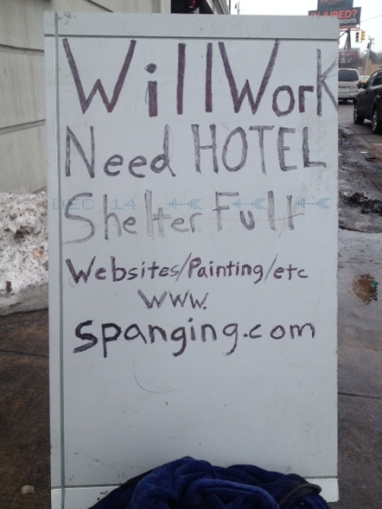 A homeless man's sign in Detroit advertises work in exchange for shelter in addition to his website spanging.com. (credit: Mike Campbell/WWJ)